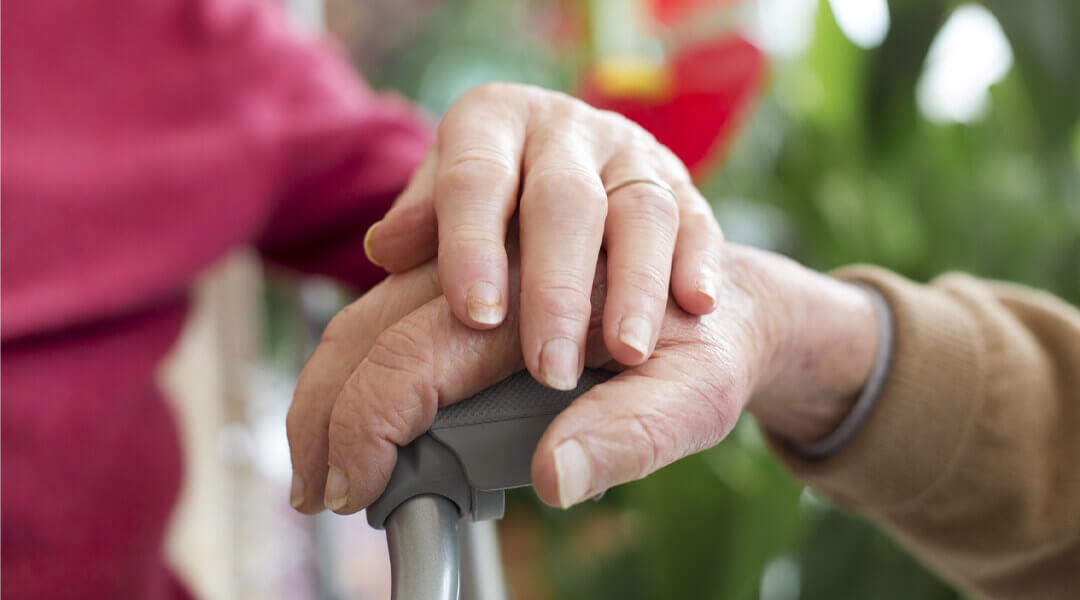 Begleitende Person die eine Patienten Hand zur Stärkung hält