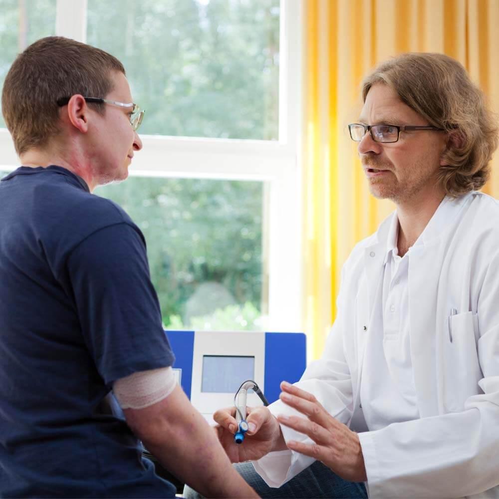 Dr. med. Hans Ziegenthaler im Gespräch mit einem Patienten über Brandverletzungen