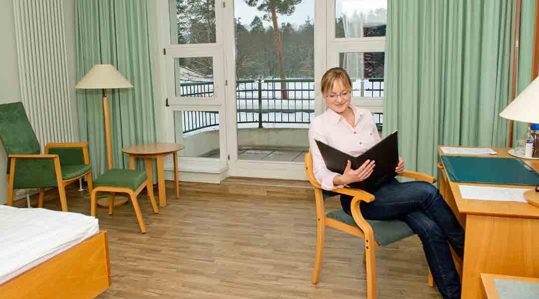 Frau liest Karte in einem Zimmer der Moritz Klinik