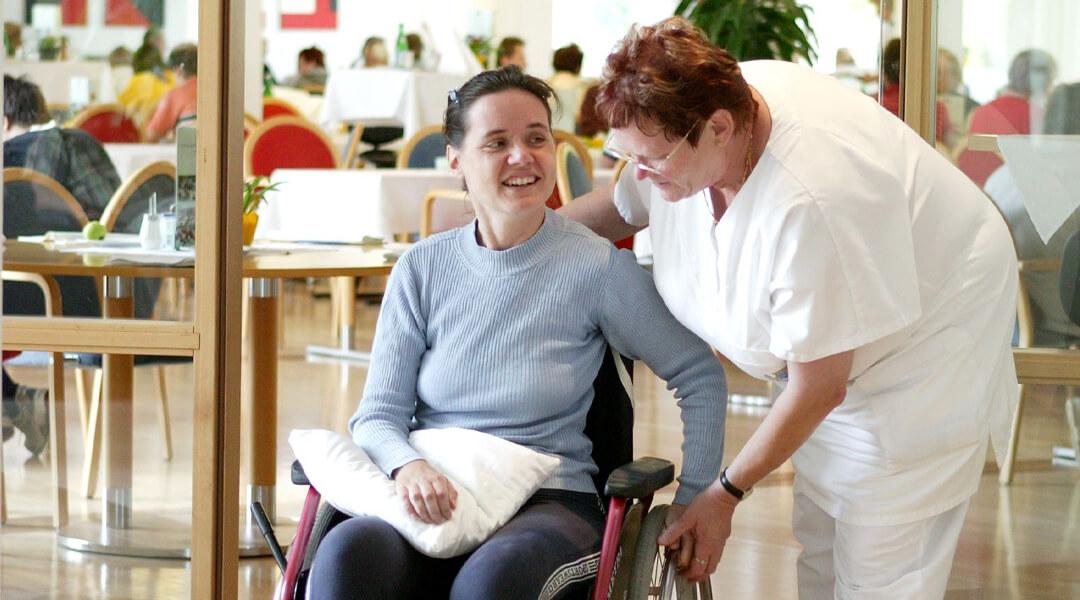 Eine Pflegerin der Moritz Klinik unterstützt eine Patientin im Rollstuhl