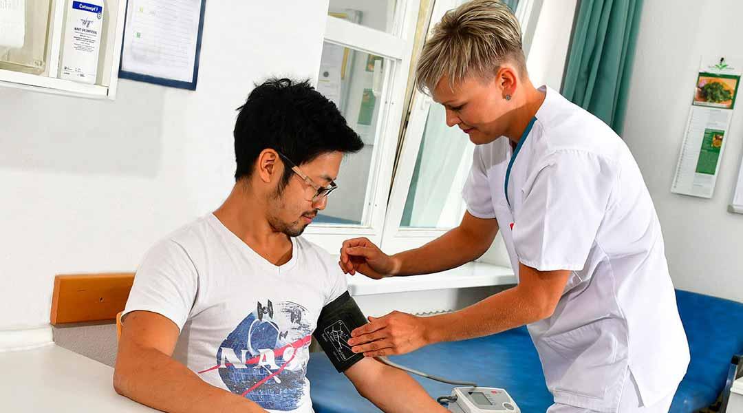 Im Behandlungsraum wird Blutdruck gemessen